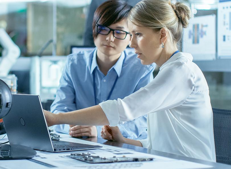 zwei kolleg:innen schauen gemeinsam auf einen laptop